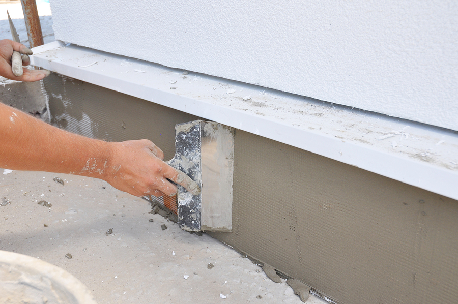 contractor plastering, repair, stucco house foundation after styrofoam insulation.