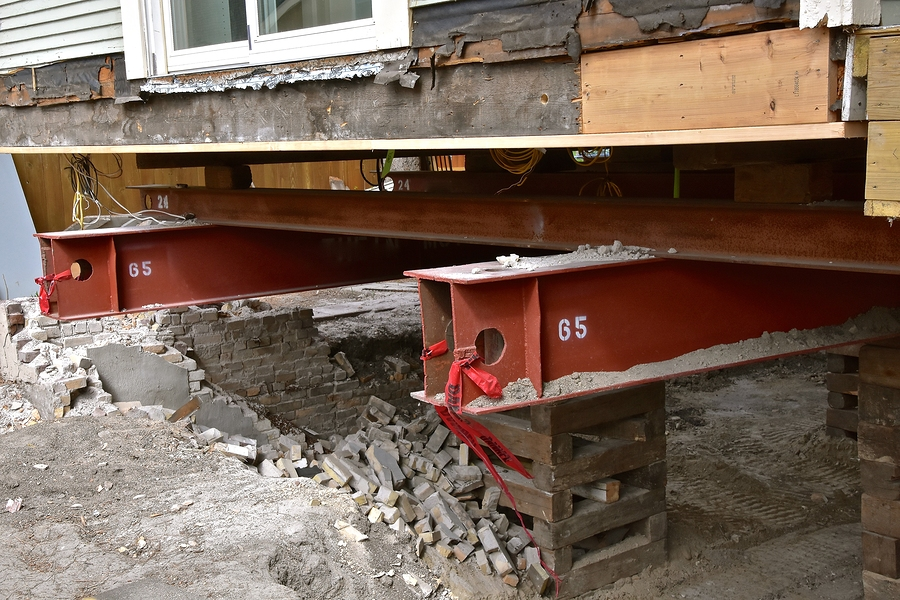 an old house rests on 65 foot long steel girders as a new concrete basement and foundation is being constructed.