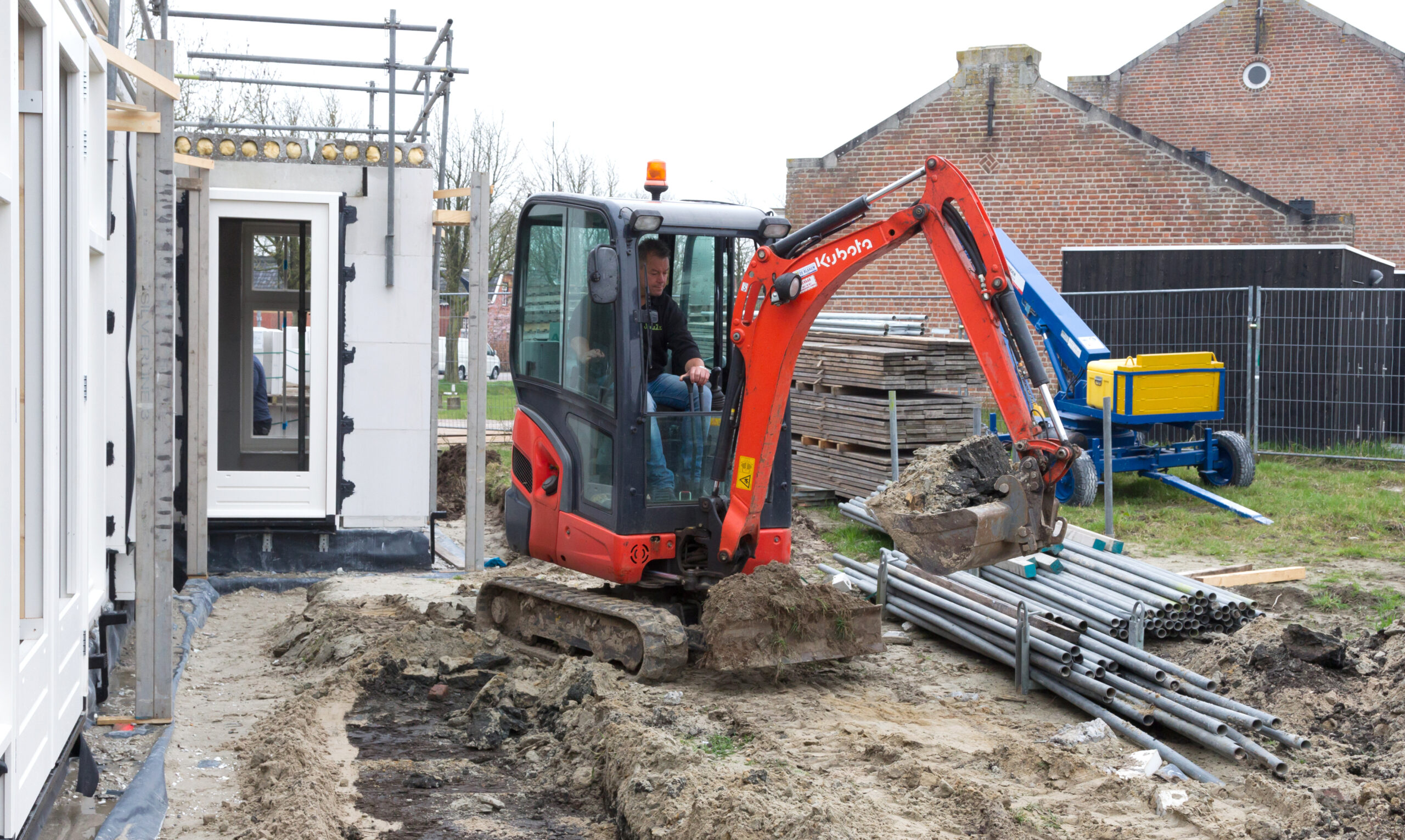 small crane is leveling ground at a building site of a dutch house